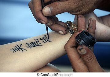 Tattoo Hand - Artist draws a tattoo henna on a female hand....