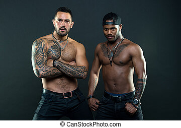 Tattoo is cool. Brutal macho style. Muscular men with fashionable tattoo style. Sexy men with muscular torso. We feel sexy