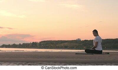Tattoo man sitting on the beach in yoga lotus pose