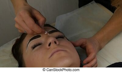 tattoo master prepares the client's eyebrows to permanent...