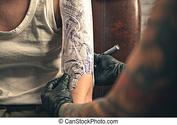 Tattoo master putting ornament on female arm
