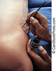 Tattoo - Artist draws a tattoo henna on a male body.