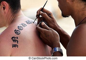 Tattoo  - Artist draws a tattoo henna on a man\'s back