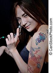 Tattoo woman artist holding tattoo machine on dark background