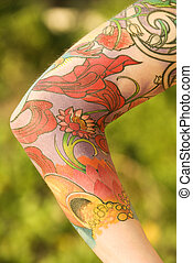 Tattooed arm. - Close up of floral tattoo on arm of...