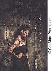 Tattooed beautiful woman in old spooky interior