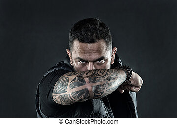Tattooed elbow hide male face. Masculinity and brutality. Tattoo culture concept. Man brutal unshaven hispanic appearance tattooed arm. Bearded man posing with tattoos. Brutal macho with tattoos