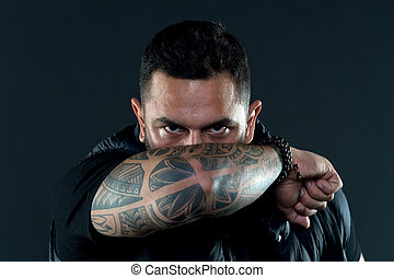 Tattooed elbow hide male face. Tattoo culture concept. Man brutal unshaven hispanic appearance tattooed arm. Bearded man posing with tattoos. Brutal macho with tattoos. Masculinity and brutality
