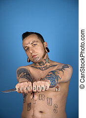 Tattooed man holding knife. - Barechested Caucasian...