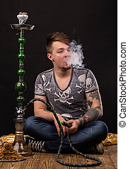 Tattooed man smoking traditional hookah. Located on a black...
