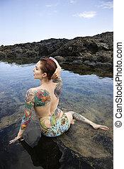 Tattooed woman in bikini. - Back view of sexy topless...