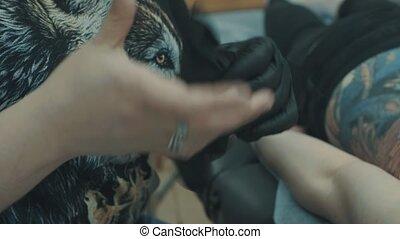 Tattooist making a tattoo on the girl's back - Master...