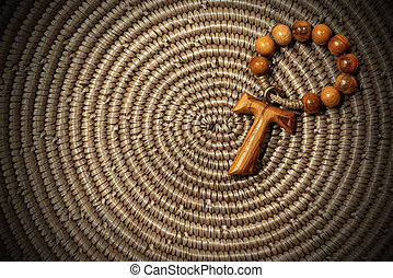Tau - Wooden Cross and Rosary Bead on woven wicker texture