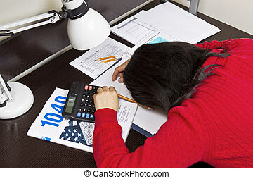 Asian woman laying face down in tax forms with pencils, calculator and lamp on desktop