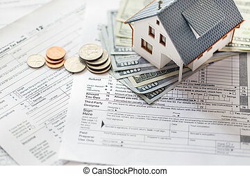 Tax forms - Miniature house with money on tax papers.