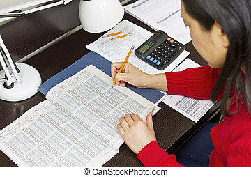 Tax Income Tables - Asian woman with pencil pointing to tax...