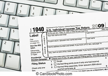 Tax papers sitting on a computer keyboard, File your taxes returns online