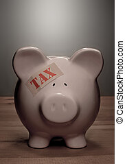 Tax - Piggy bank with tax band aid