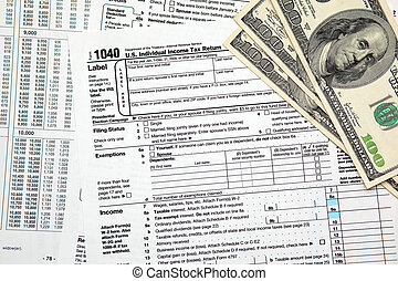 Tax time - Closeup of U.S. 1040 tax return with $100 bills