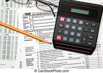 Tax time - Closeup of U.S. 1040 tax return with pencil, glasses and calculator