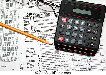 Tax time - Closeup of U.S. 1040 tax return with pencil, glasses and calculator