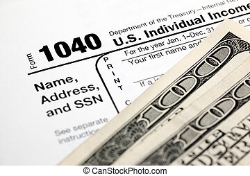 Tax time - Closeup of U.S. 1040 tax return with $100 bills