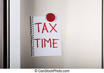 Tax Time Note Attached With Magnetic Thumbtack On Wall