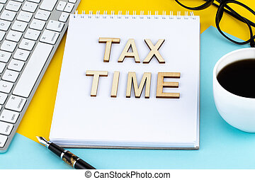 Tax Time - wooden letters with tax form, and cup of coffee
