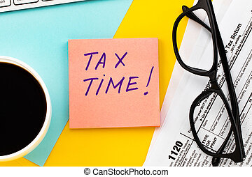Tax Time written on paper note with tax form, and cup of coffee