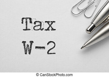 Tax W-2 words printed with typewriter, pen and paper clips