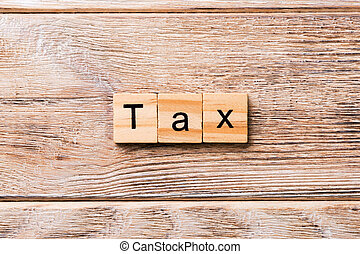 Tax word written on wood block. Tax text on wooden table for your desing, concept