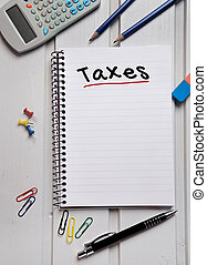Taxes word on notebook