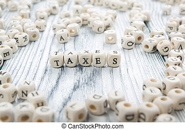 Taxes word written on wood block. Wooden ABC.