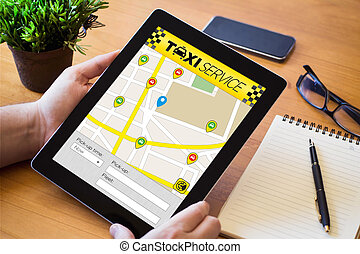 taxi app tablet on wooden workspace