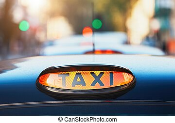 Taxi cars on the street - London black taxi cab sign on the...