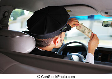 Taxi driver checking dollar bill