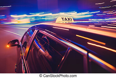 Taxi taking a left turn at night in an urban surrounding,...