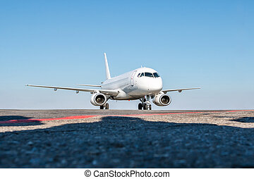 Taxiing a white passenger jet plane on the airport apron