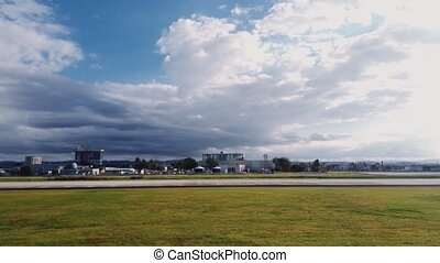 Taxiing on the runway at a tropical airport during a cloudy day