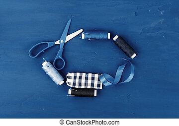 Tayloring accessories on classic blue background, top view