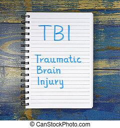 TBI- Traumatic Brain Injury acronym written in notebook on...
