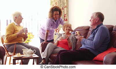 Three seniors enjoying tea and cake with their care home worker.
