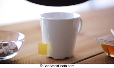tea bag and hot water pouring from kettle to cup