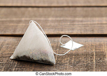 tea bag pyramid closeup on a brown wooden table. space for text