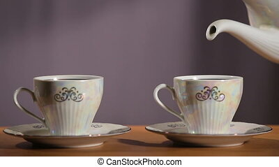 Tea being poured into cup - Teapot pouring tea into a...