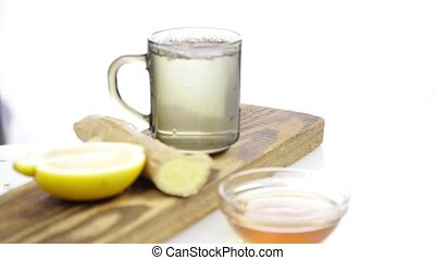 Tea being poured into glass transparent tea cup with lemon and ginger. Warming drink in cold weather