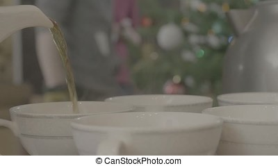 Tea being poured into tea cup. Kettle pours tea into cups