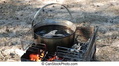 tea boil in a large saucepan on fire in the open air.
