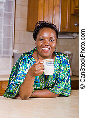 tea break - african woman taking a tea break in the kitchen
