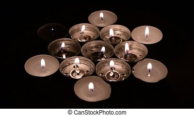 Tea candles rotation on a mirror background with camera moves from left side to the right